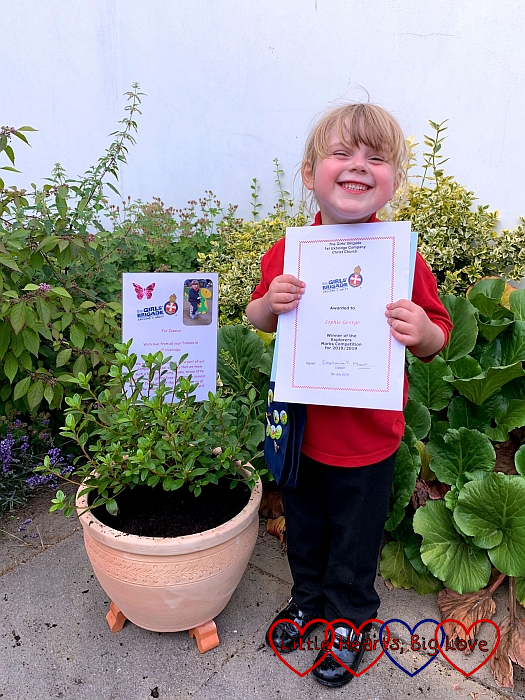 Sophie holding her certificate from Girls' Brigade and standing next to the azalea planted in memory of Jessica