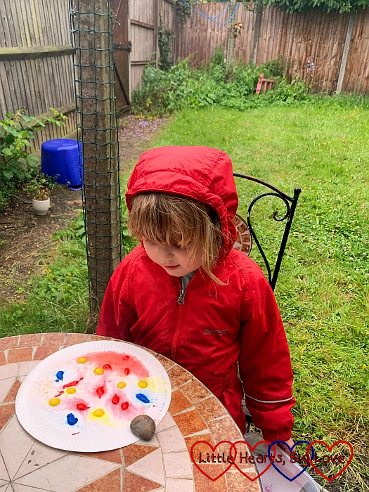 Sophie in her puddle suit looking at the rain splattering paint drops on a paper plate
