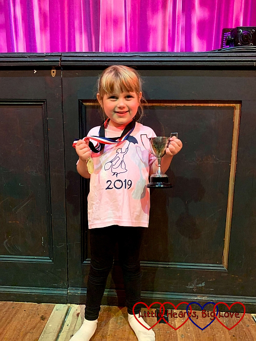 Sophie in her ballet show T-shirt holding her medals for doing the show and her trophy