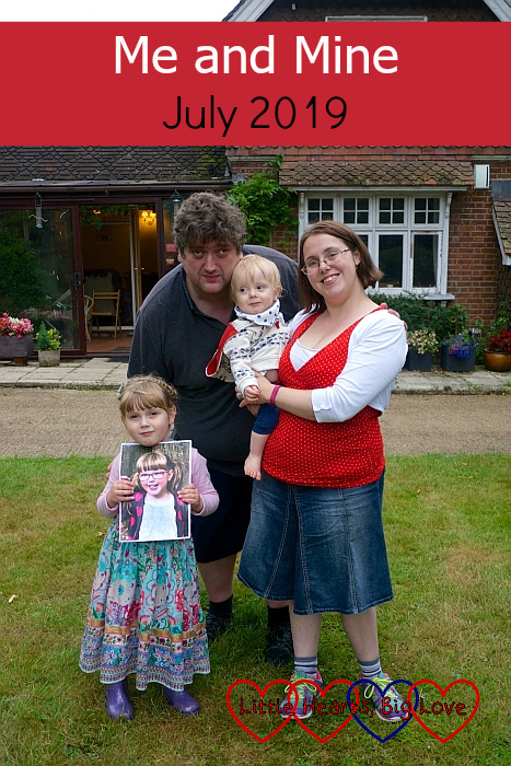 "Me (holding Thomas), hubby and Sophie (holding Jessica's picture) in Grandma and Grandad's garden at Thomas's birthday party - ""Me and Mine - July 2019"""