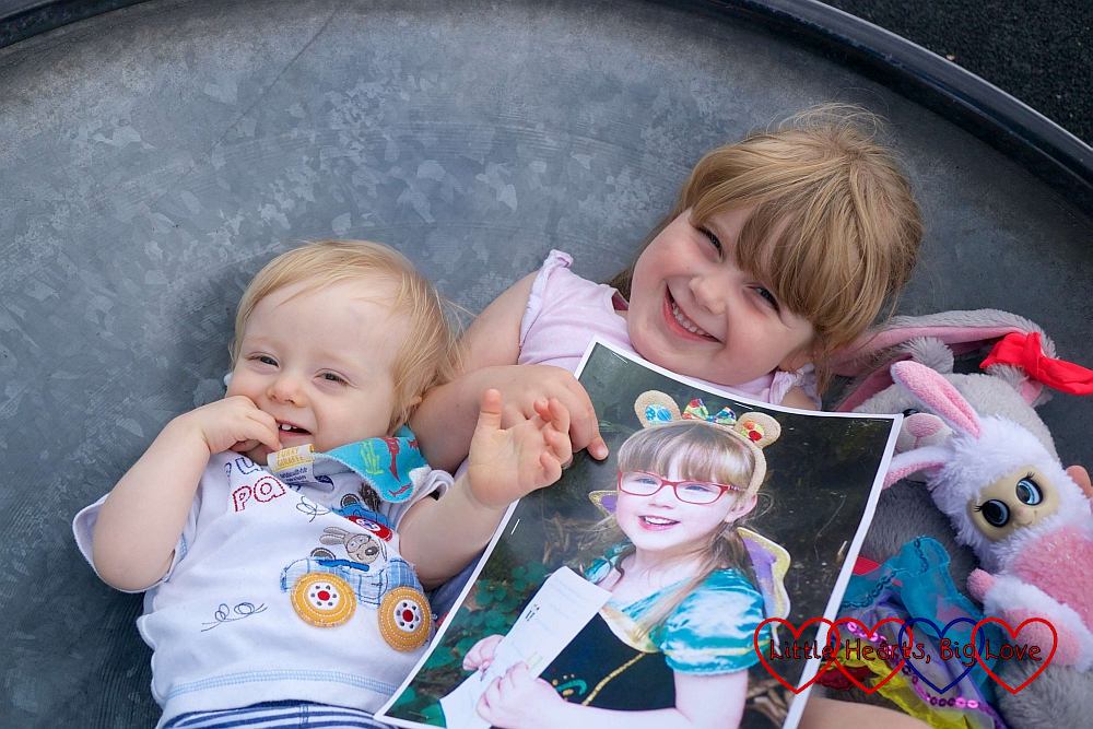 Thomas and Sophie holding a picture of Jessica in a spinning saucer