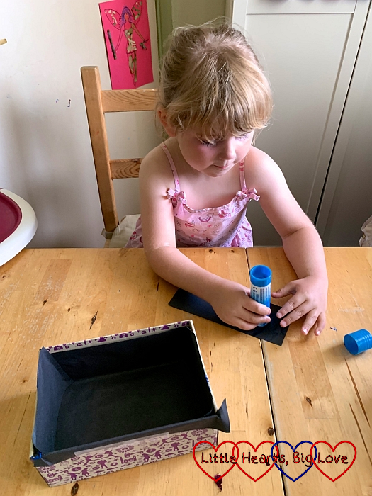 Sophie sticking black paper inside the small shoebox