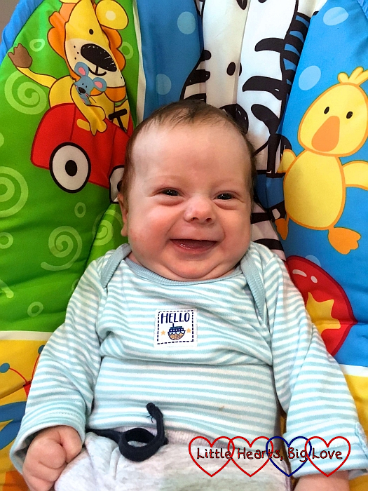 Baby Thomas sitting in his swing smiling