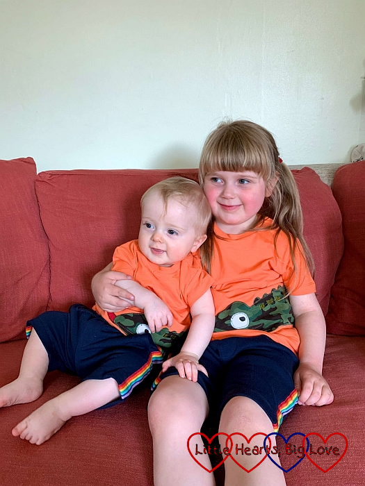 Thomas and Sophie on the sofa wearing matching orange T-shirts and blue shorts