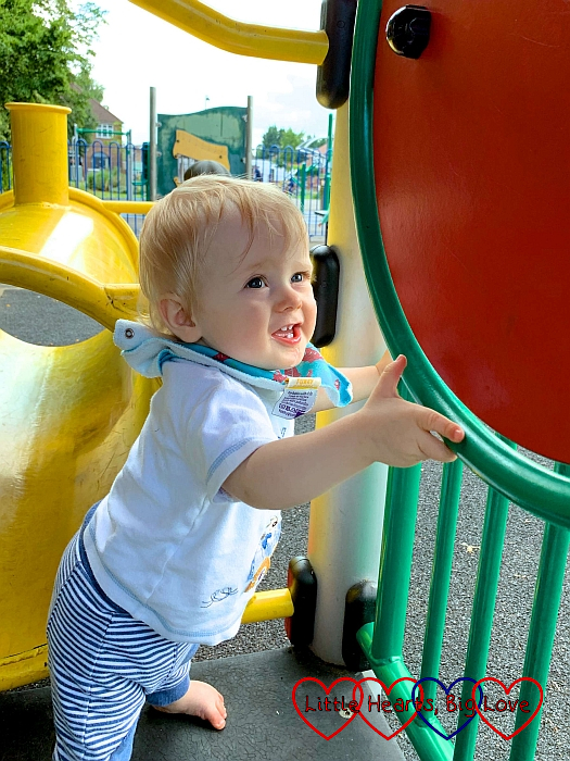 Thomas standing up at the park and spinning a disc on the baby play equipment