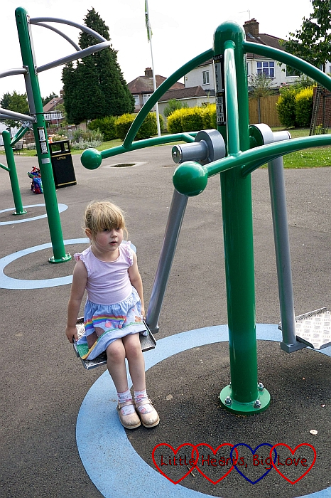 Sophie sitting on one of the outdoor gym pieces of equipment