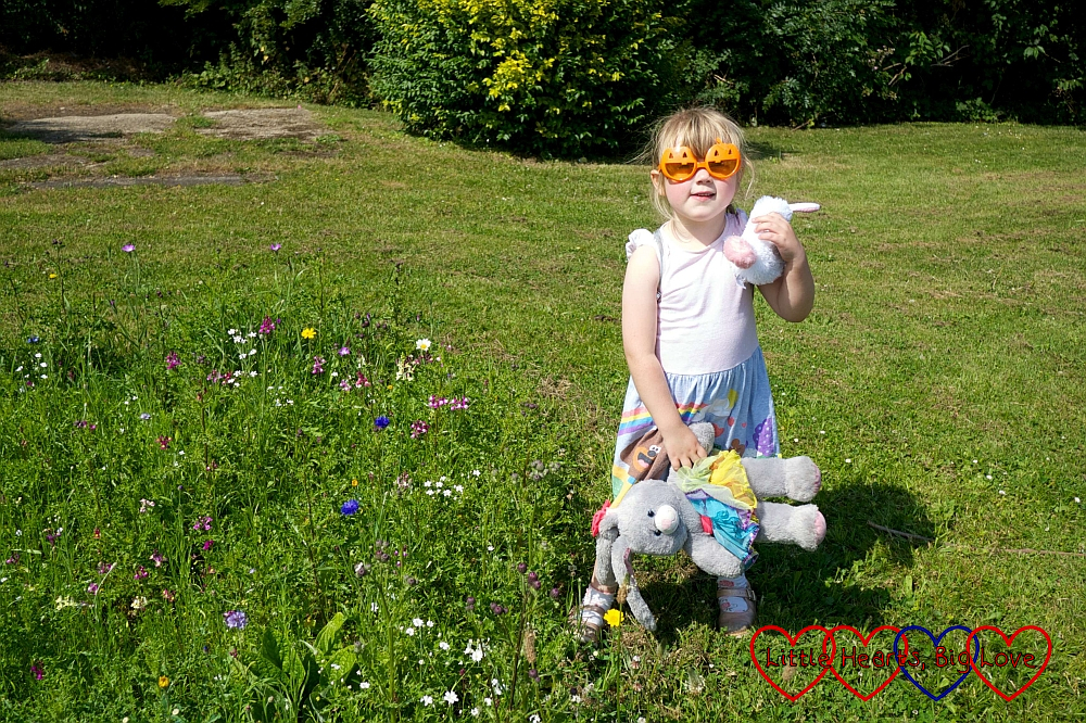 Sophie wearing pumpkin sunglasses next to the wildflower area