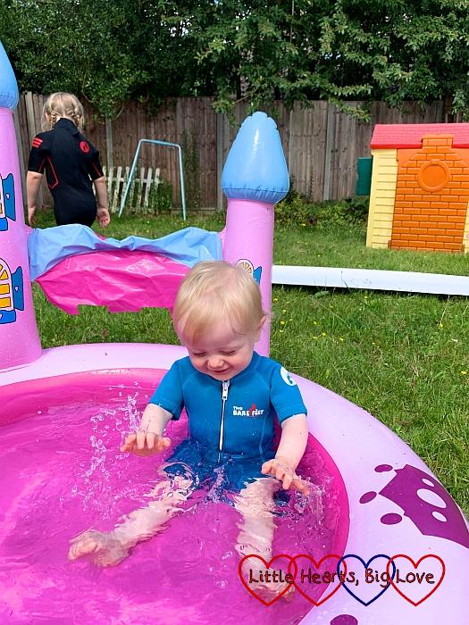 Thomas splashing in the paddling pool
