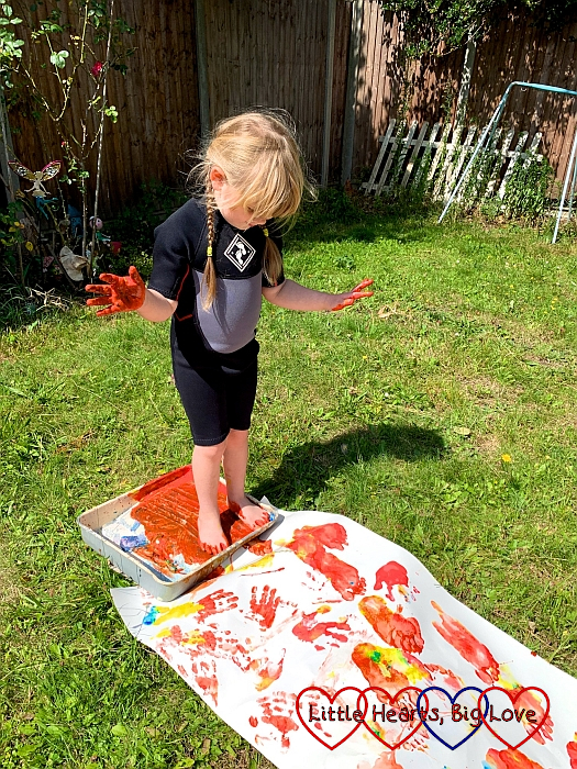 Sophie standing in a paint-filled tray about to step on a piece of lining paper covered in footprints