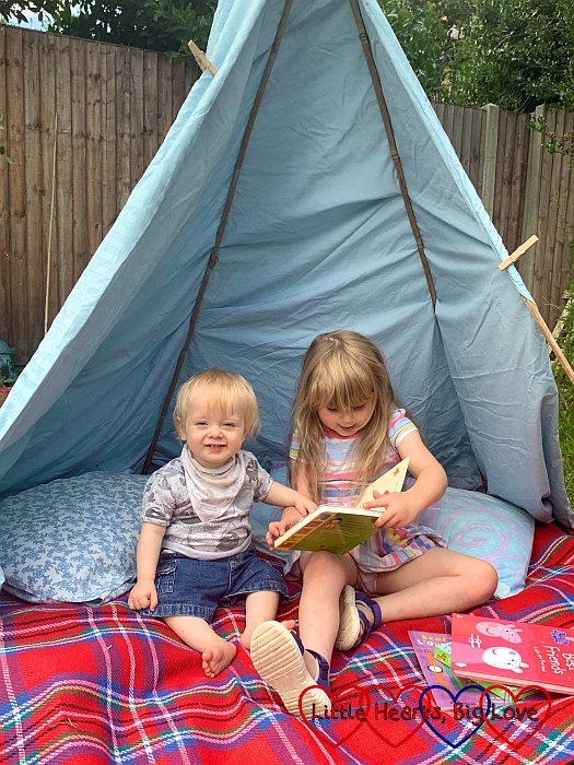 Sophie and Thomas sitting in a home-made tepee looking at books together