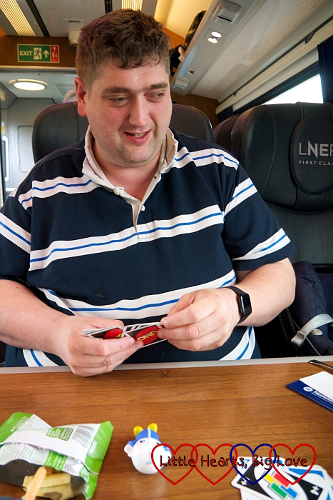 Hubby on the train playing UNO with Sophie