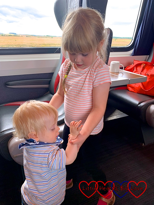 Sophie holding Thomas's hands on the train and helping him walk up and down the carriage