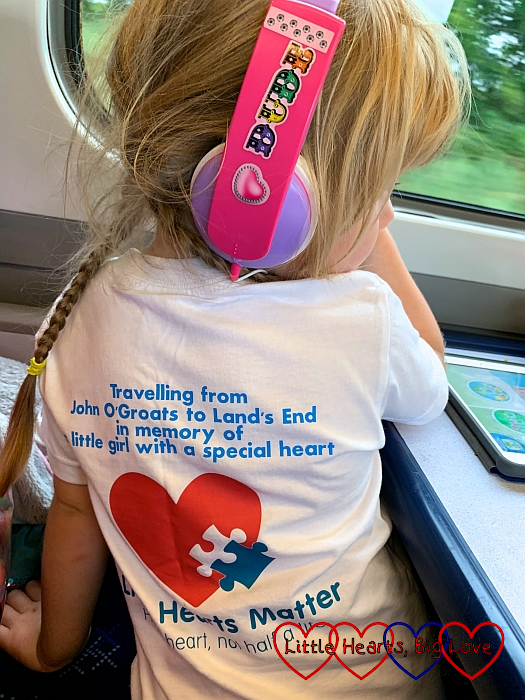 "Sophie showing the text on the back of her JoGLE for Jessica T-shirt ""Travelling from John O'Groats to Land's End in memory of a little girl with a special heart"" with the Little Hearts Matter logo beneath the text"