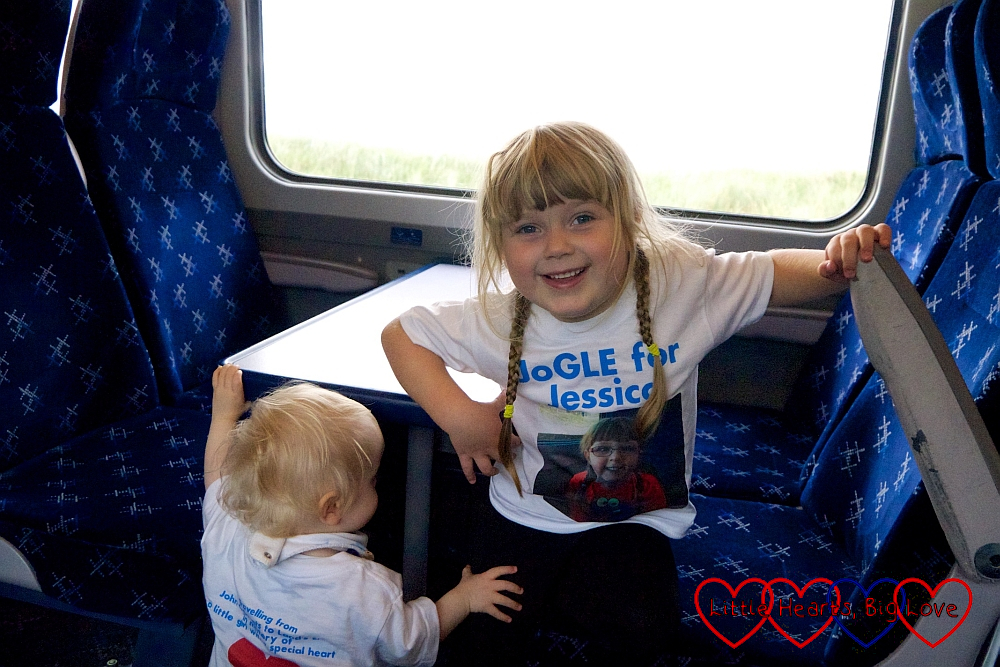 Sophie and Thomas (wearing their JoGLE for Jessica T-shirts) on the train to Wick