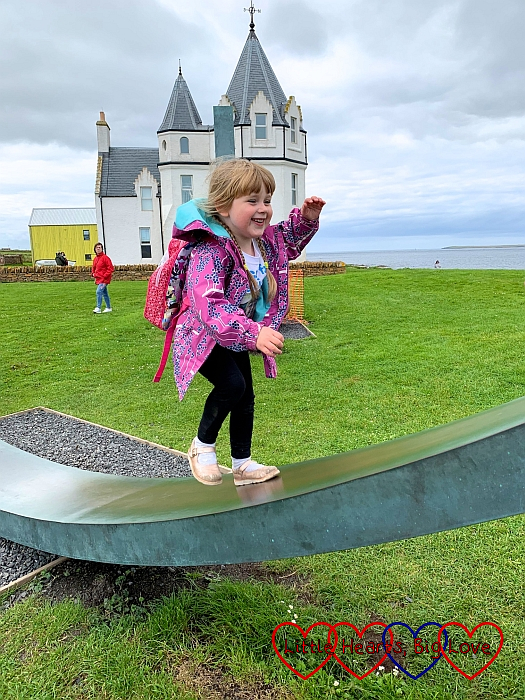 Sophie walking up one of the metal arc sculptures at John O'Groats