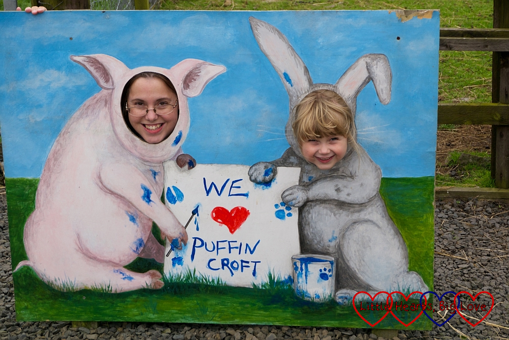 "Me and Sophie with our heads through a picture of a pig and a rabbit and the text ""We love Puffin Croft"""
