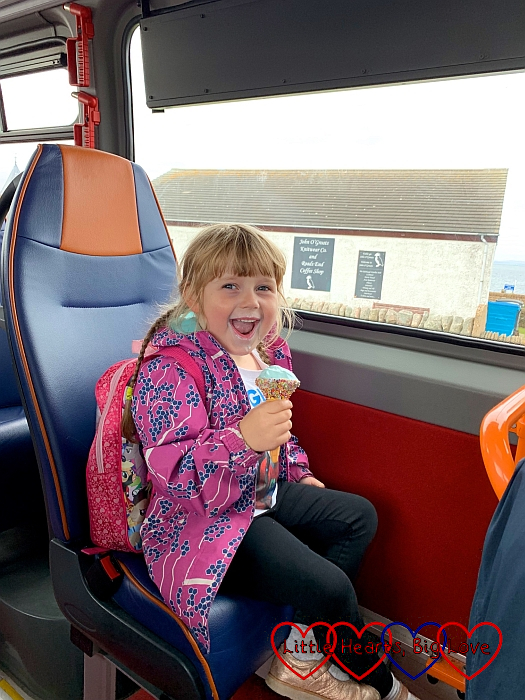 Sophie sitting on the bus at John O'Groats eating an ice-cream