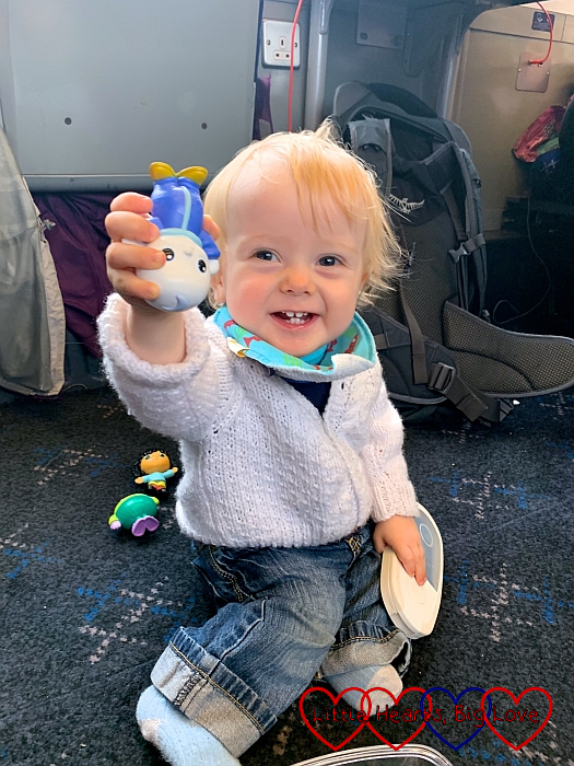 Thomas sitting on the floor of the train carriage holding up one of his 'Moon and Me' toys