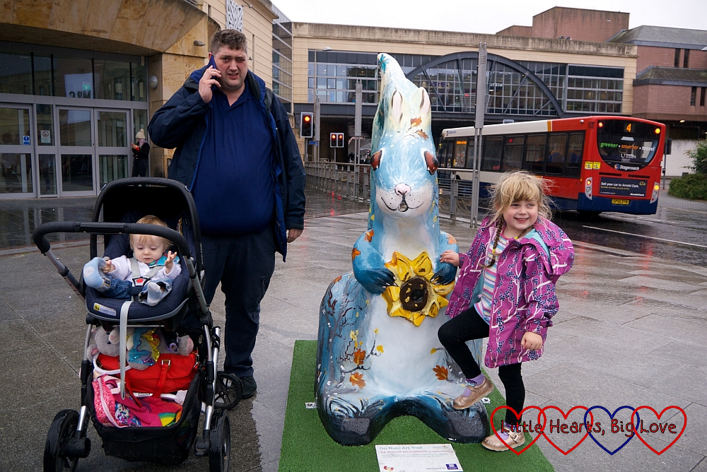 Hubby, Thomas and Sophie next to a painted squirrel sculpture in Inverness