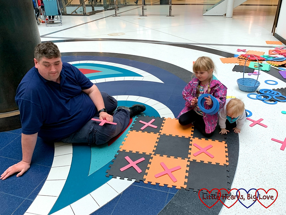Hubby and Sophie playing noughts and crosses at the Eastgate shopping centre