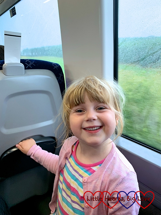 A smiley Sophie sitting on the train