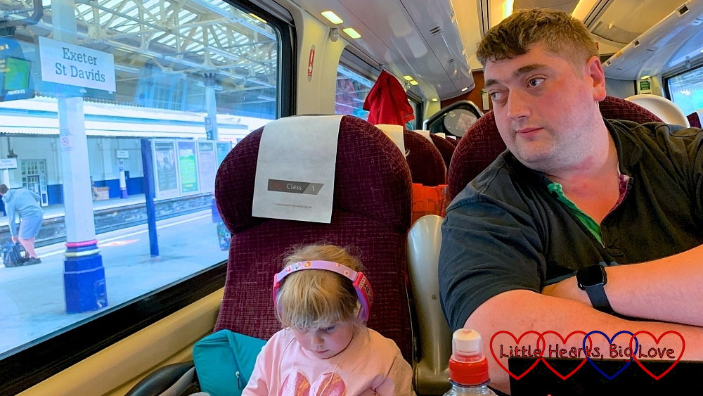 Sophie sitting on the train with her headphones on while hubby looks out of the window at Exeter St David station