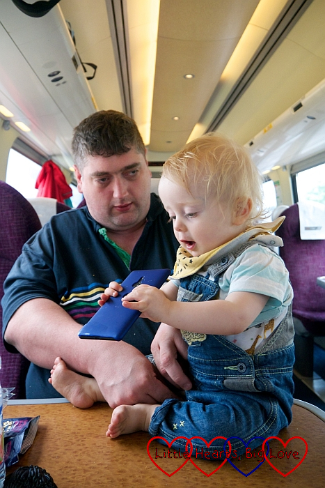 Hubby holding Thomas on the train - Thomas is holding hubby's phone