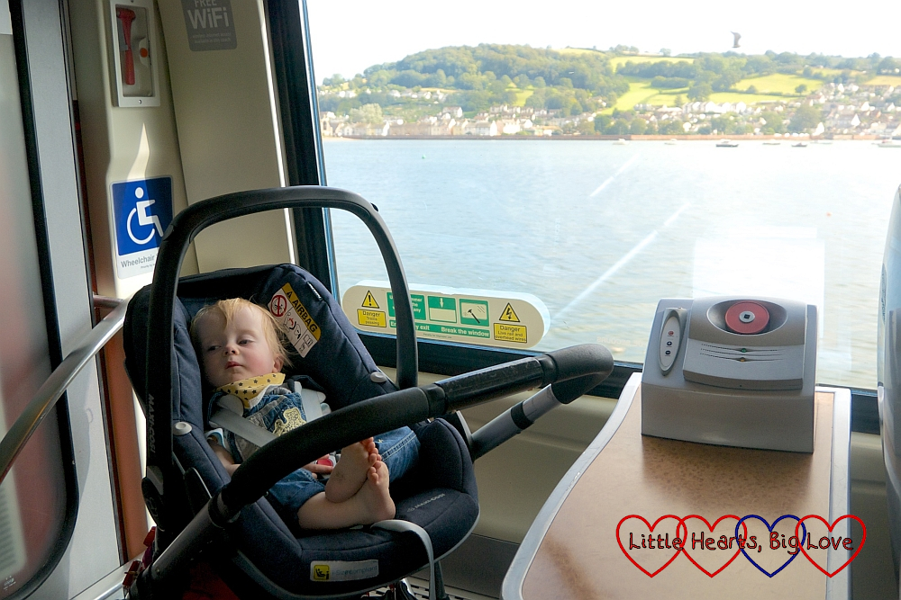 Thomas asleep in his car seat on the train with a view out to sea