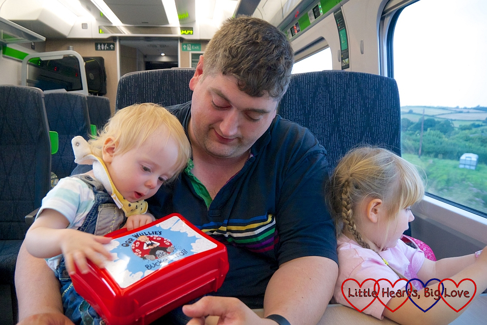 Thomas (holding Sophie's Oor Wullie lunchbox), hubby and Sophie (looking out of the window) on the train