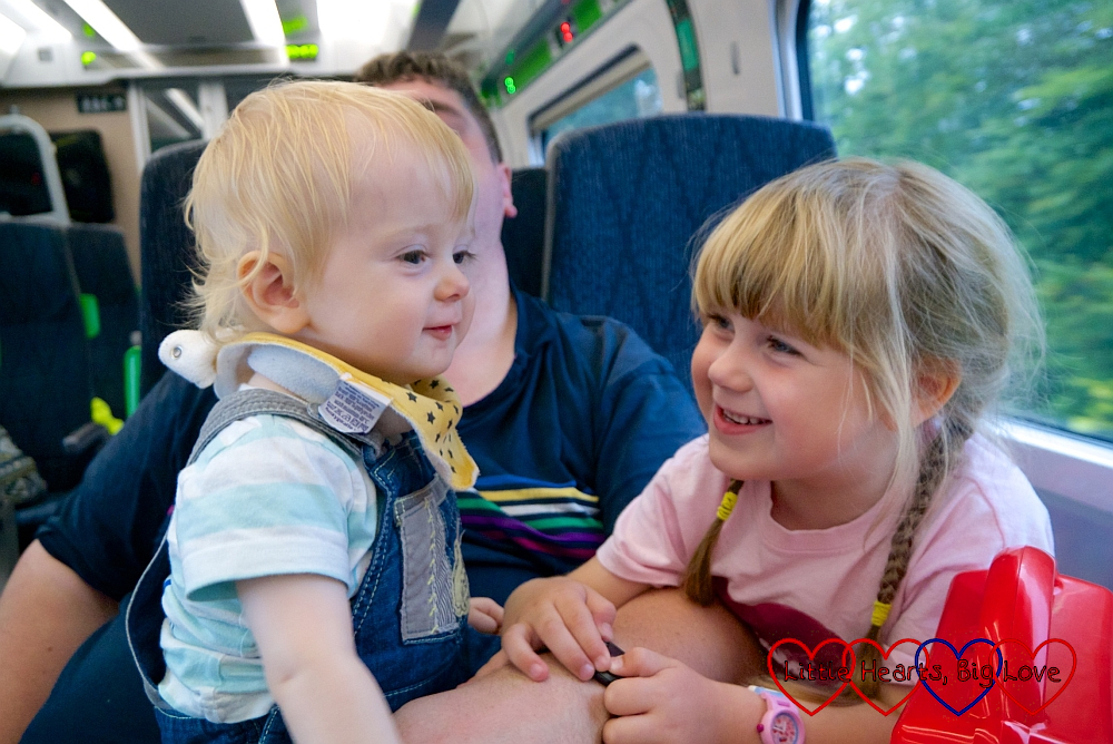 Thomas and Sophie sitting on the train and looking at each other