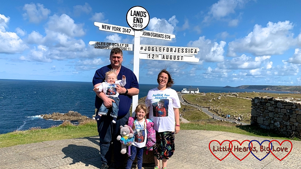 """Me, hubby, Sophie and Thomas wearing our """"JoGLE for Jessica"""" T-shirts at the Land's End signpost with """"JoGLE for Jessica 12th August"""" added to the signpost"""