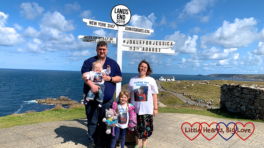 "Me, hubby, Sophie and Thomas wearing our ""JoGLE for Jessica"" T-shirts at the Land's End signpost with ""JoGLE for Jessica 12th August"" added to the signpost"