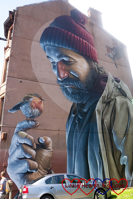 A mural on the side of a building showing a man in a woolly hat holding a robin with another robin on his shoulder