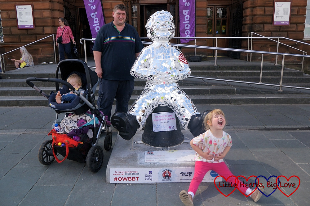 Hubby, Sophie and Thomas with the 'Oor Wullie Reflects' Oor Wullie sculpture outside the People's Palace with Sophie copying the Oor Wullie pose