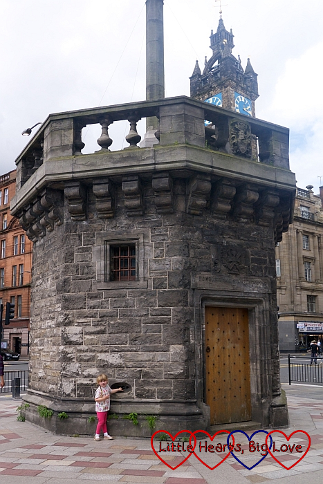 Sophie standing in front of the Mercat Cross in Glasgow Cross