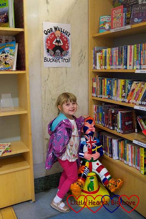 Sophie with the 'Oor Wullie's World' Wee Oor Wullie sculpture in the GOMA library