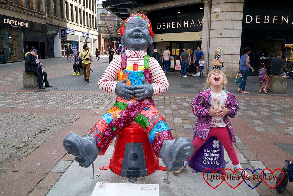 Sophie sitting next to the 'Scott's Snashters' Oor Wullie sculpture and copying the pose