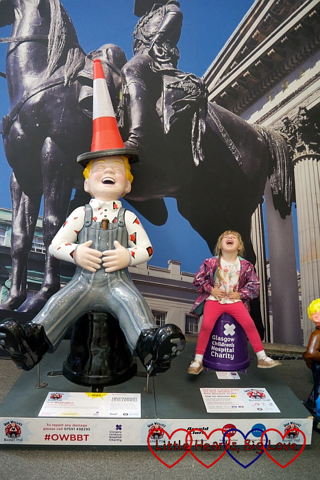 Sophie with the 'Oor Wullington' Oor Wullie sculpture and copying the pose