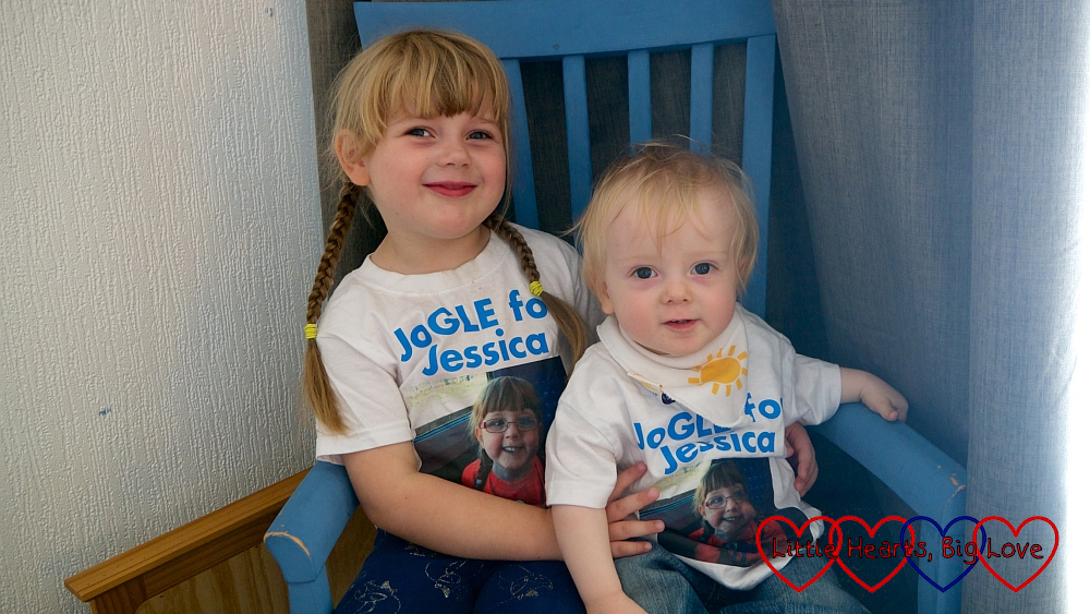 "Sophie and Thomas sitting in a blue chair wearing their ""JoGLE for Jessica"" T-shirts"