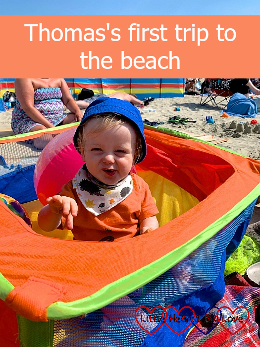 Thomas sitting in his colourful pop-up ball pit on the beach at West Wittering