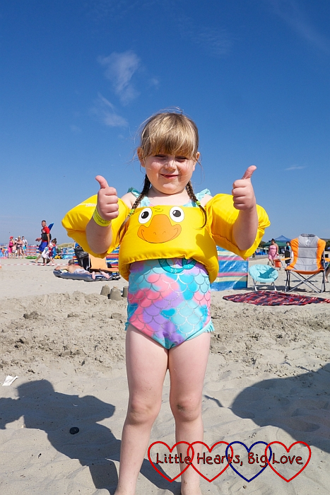 Sophie standing on the beach wearing her duck flotation aid and giving me a thumbs up