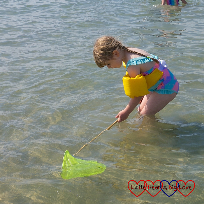 Sophie fishing with her yellow fishing net in the sea
