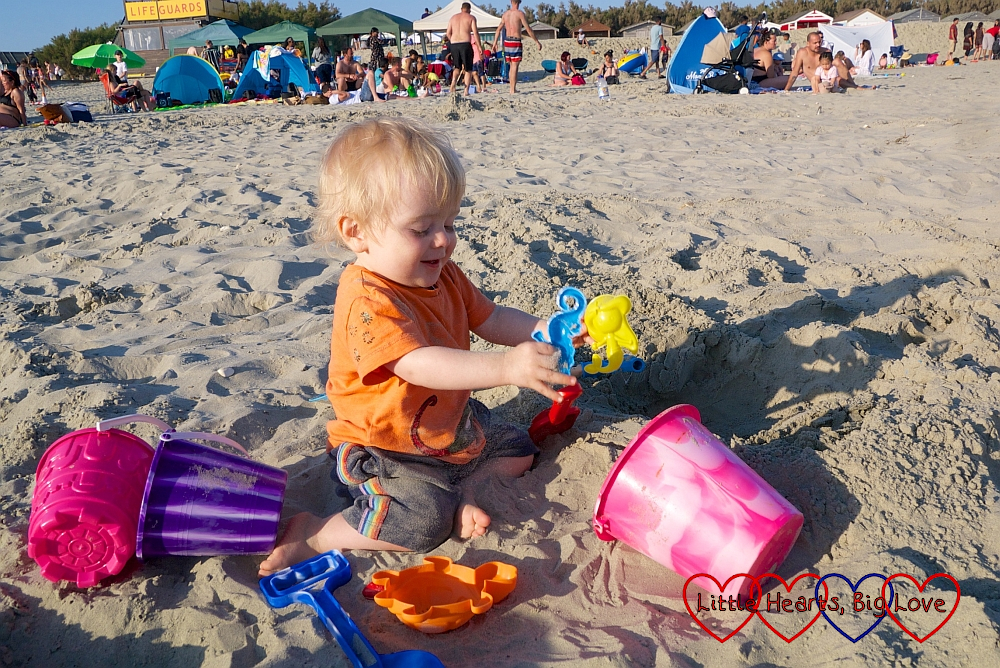 Thmas playing with buckets and spades in the sand