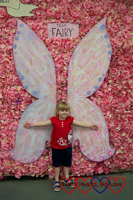Sophie standing in front of pink fairy wings on a wall