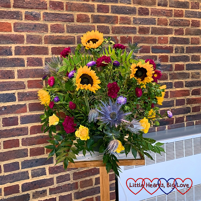 A flower arrangement at church in memory of Jessica with sunflowers, deep red and purple asters and carnations, and yellow roses