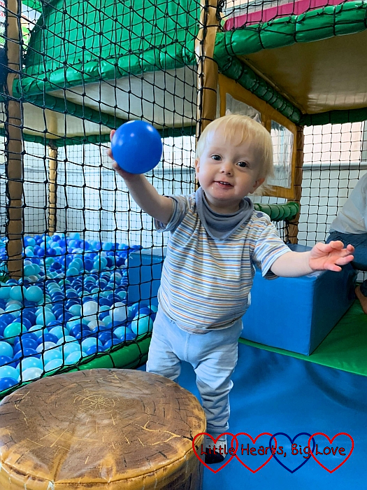 Thomas standing in the soft play and holding a blue ball in the air