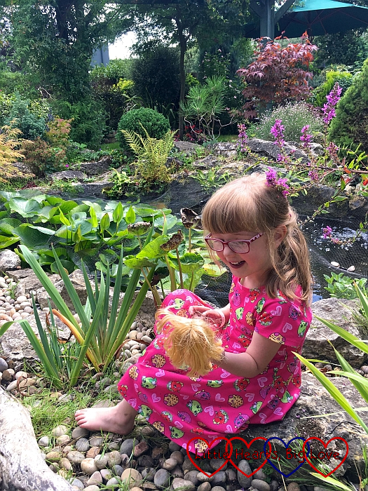 Jessica sitting by a pond at the garden centre holding one of her Lottie dolls