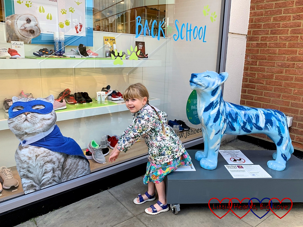Sophie doing a cat pose next to a picture ofSophie doing her best cat pose in between a picture of a cat wearing a blue superhero mask and cape in the window of a shoe shop and the 'Lambrook' lion sculpture in Windsor