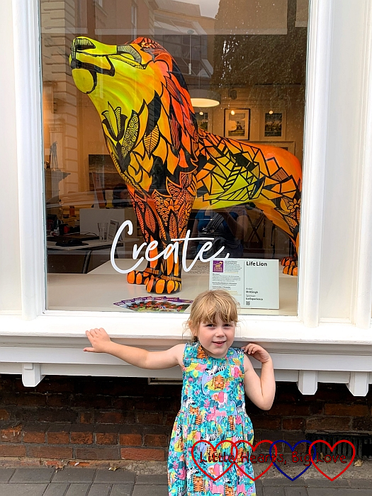 Sophie in front of a window with the 'LifeLion' lion sculpture in the window behind her