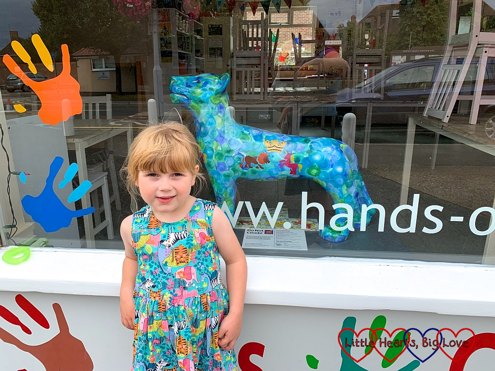 Sophie standing in front of a shop window containing the 'Prints Owen of Old Windsor' lion sculpture